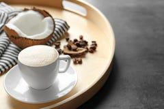 Vassoio con la tazza del caffè e del dado saporiti della noce di cocco Fotografie Stock
