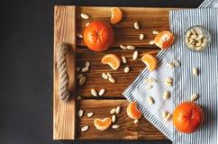 Vassoio con un tovagliolo fatto del panno, dei mandarini e delle arachidi immagini stock