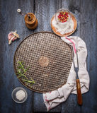 Vassoio d'acciaio di cottura con un tovagliolo, una forcella e le spezie su fondo di legno rustico immagine stock libera da diritti