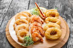 Vassoio dei frutti di mare con gli anelli del calamaro, il gamberetto fritto nel grasso bollente e gli anelli di cipolla decorati Immagine Stock Libera da Diritti