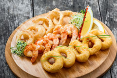 Vassoio dei frutti di mare con gli anelli del calamaro, il gamberetto fritto nel grasso bollente e gli anelli di cipolla decorati Immagini Stock
