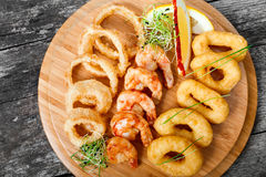 Vassoio dei frutti di mare con gli anelli del calamaro, il gamberetto fritto nel grasso bollente e gli anelli di cipolla decorati Immagini Stock Libere da Diritti