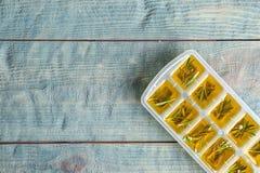 Vassoio del cubetto di ghiaccio con i rosmarini e l'olio d'oliva su fondo di legno, vista superiore fotografie stock libere da diritti