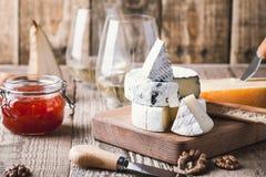 Vassoio del formaggio con vino, inceppamento e le noci sul bordo di legno fotografia stock