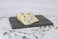 Vassoio del formaggio dell'ardesia con una fetta di formaggio blu del Bleu con il latte della pecora immagine stock