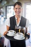 Vassoio del servizio della tenuta della cameriera di bar con la tazza di caffè e la pinta di birra Immagine Stock