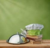 Vassoio dell'alimento, cuoco unico del cappuccio e libro di cucina su un fondo d'annata verde Fotografie Stock