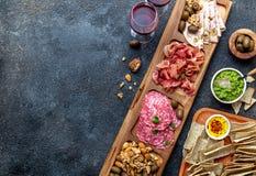 Vassoio dell'antipasto Serrano del prosciutto, salse verde oliva della immersione del jamon del salame e vino rosso fotografia stock