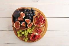 Vassoio della frutta - fichi, uva, melograno su fondo di legno Fotografia Stock