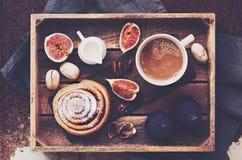 Vassoio della prima colazione - tazza di caffè con crema, il rotolo di cannella, i fichi freschi ed i pecan fotografie stock