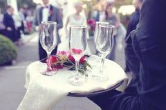 Vassoio della tenuta del cameriere con i vetri del champagne fotografie stock libere da diritti