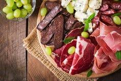 Vassoio di approvvigionamento dell'antipasto con bacon, a scatti, la salsiccia, il formaggio blu e l'uva fotografie stock libere da diritti