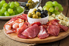 Vassoio di approvvigionamento dell'antipasto con bacon, a scatti, salame, formaggio e l'uva Fotografia Stock