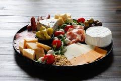 Vassoio di Chesse con formaggio, prosciutto di Parma, pomodoro, dadi Cibo sano, latteria, chesses e carne Aperitivo dei Antipasti fotografie stock