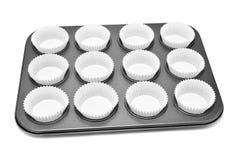 Vassoio di cottura con le tazze di carta per i muffin o i bigné Fotografie Stock