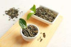 Vassoio di legno con tè e le foglie verdi asciutti fotografia stock libera da diritti