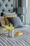 Vassoio di libro con il vaso della pianta sul letto in camera da letto di lusso Immagini Stock