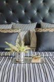 Vassoio di libro con il vaso della pianta sul letto in camera da letto nera di lusso Immagine Stock