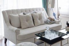 Vassoio di vetro sulla tavola con il sofà beige di colore in salone fotografia stock libera da diritti