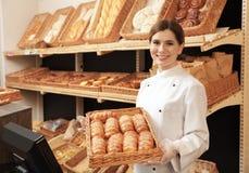 Vassoio professionale della tenuta del panettiere con i panini freschi fotografie stock libere da diritti