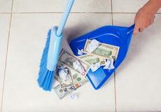 A vassoura da mulher varre dólares na colher do lixo no fundo do assoalho fotografia de stock royalty free