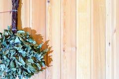 Vassoura de vidoeiro seca para o banho do russo que pendura em uma parede de madeira imagens de stock