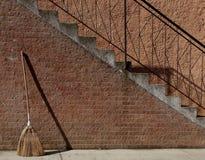 Vassoura que inclina-se contra uma parede de tijolo Fotografia de Stock Royalty Free