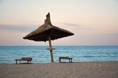 Vassparaply på stranden i solnedgång Fotografering för Bildbyråer