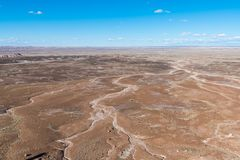 Vast barren desert landscape with an abstract pattern of dry stream and river beds under a beautiful blue sky stock image