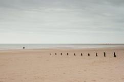 Holkham, Norfolk, UK: Vast empty beach and horizon under winter sky. Vast beach and horizon with weathered groynes, Norfolk, UK Royalty Free Stock Images