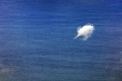 Loneliness over the blue ocean. The vast blue ocean with a solitary little white cloud stock image