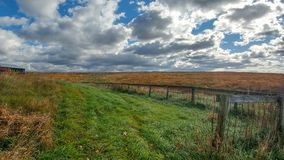 Vast Farmland with fence and Cloudy Sky. A vast and open farm field with a fence and a gorgeous cloud filled sky on a stormy, partly sunny day in Wisconsin royalty free stock photo