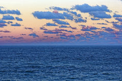 Vast ocean landscape and drifting clouds by sunset sky. The dark-blue waters of the rough sea and the blue clouds by a pink sunset sky. The Pacific Ocean at Stock Photo
