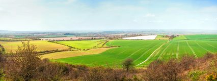 Vast panorama landscape with ultra high resolution. Representing open fields with spring crops fresh green colours blue skies and a rural village in the horizon royalty free stock photography