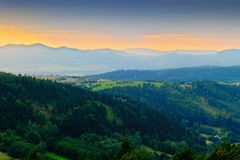Vast panorama view of foggy valley in the Owl Mountains with silhouette of Sudetes mountain range at dusk. Poland. Royalty Free Stock Photo