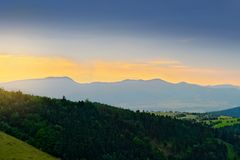 Vast panorama view of foggy valley in the Owl Mountains with silhouette of Sudetes mountain range at dusk. Poland. Stock Photo