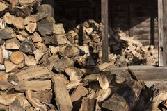 Fire Wood Pile in a Shed. A vast pile of chopped wood piled up inside an old shed ready for winter fueling Stock Photos