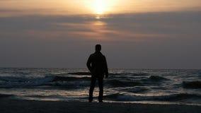 Vast statisch silhouet van de mens bij avond overzeese kust vóór zonsondergang stock footage