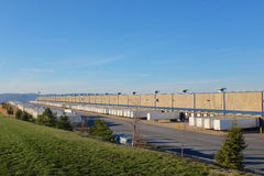 Vast Warehouse and Tractor Trailers. A vast warehouse and seemingly endless row of tractor trailers is shown expressing and symbolic of expansive and successful Stock Photos