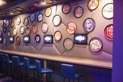Vasta varietà degli emblemi e dei marchi di fabbrica unici della birra da ogni parte del mondo disposto su esposizione in birra A Immagini Stock