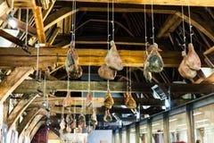 Vastgehaakte ham op houten stralen die van het plafond hangen Traditionele manier om vlees te drogen Varkensvleesham het drogen o royalty-vrije stock afbeelding