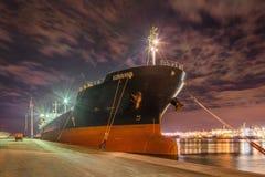 Vastgelegde olietanker bij nacht met een dramatische bewolkte hemel, Haven van Antwerpen, België Stock Afbeelding