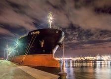 Vastgelegde olietanker bij nacht met een dramatische bewolkte hemel, Haven van Antwerpen, België Stock Foto