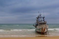 Vastgelopen vissersboot op het strand stock foto's