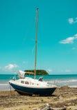 Vastgelopen zeilboot op verlaten eiland Stock Foto's