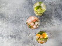 Vastgestelde de zomer koude dranken met verschillende citrusvrucht in glazen op een grijze achtergrond Cocktail met grapefruit, s Stock Foto's