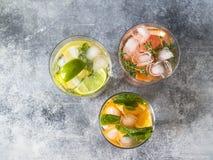 Vastgestelde de zomer koude dranken met verschillende citrusvrucht in glazen op een grijze achtergrond Cocktail met grapefruit, s Stock Afbeelding