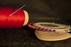 Vastgestelde kleermaker: rode draad met een naald, wit krijt voor tekening Stock Foto