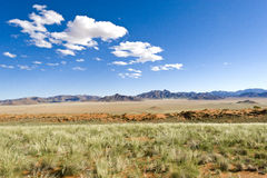 Vastness in Namibia. With green grass, orange dunes, blue mountains and blue sky with white clouds Stock Images