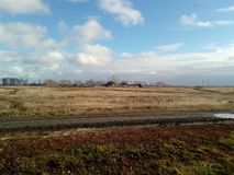The vastness of Russia the autumn chill October November September after a rain the Russian fields Russian village in autumn. Blue sky with white clouds blowing Royalty Free Stock Image
